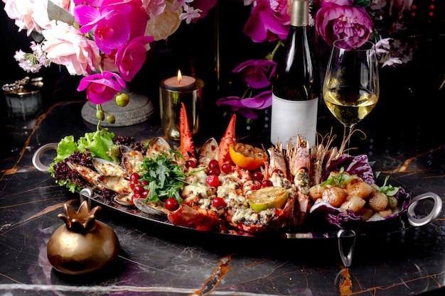 Gorący talerz owoców morza z homarem, ostrygą, krewetkami tygrysimi i przegrzebkami