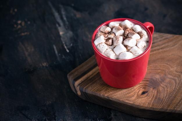 Gorący zimowy lub jesienny napój, gorąca czekolada lub kakao, pianka piankowa i sweter z dzianiny