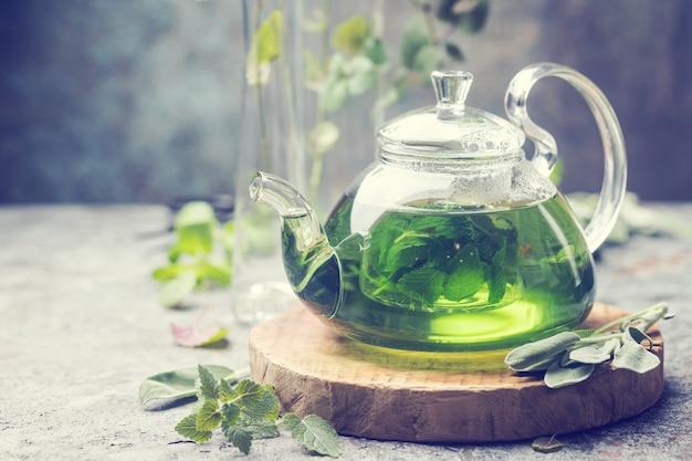 Gorący ziołowy napój herbaciany o działaniu uspokajającym w szklanym czajniczku na drewnianej tacy ze świeżą miętą ogrodową