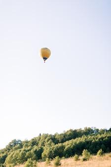 Gorący żółty balon wysoko na niebie, latający w pięknym zielonym letnim polu o zachodzie słońca