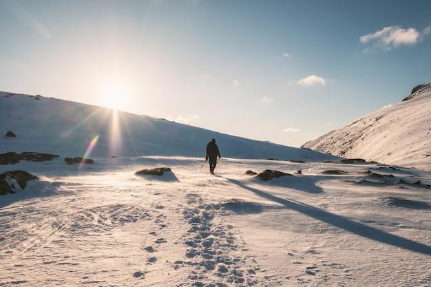 Góral chodzenie po zaśnieżonej górze ze światłem słonecznym na ryten mount