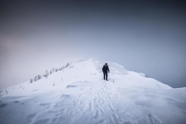 Góral człowiek chodzenie na śnieżny grzbiet górski z zamiecią w ponurej pogodzie na wyspie senja, norwegia