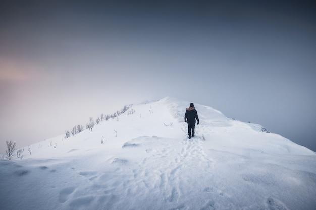 Góral człowiek chodzenie po zaśnieżonym grzbiecie górskim z zamiecią śnieżną w ponurej pogodzie na wyspie senja