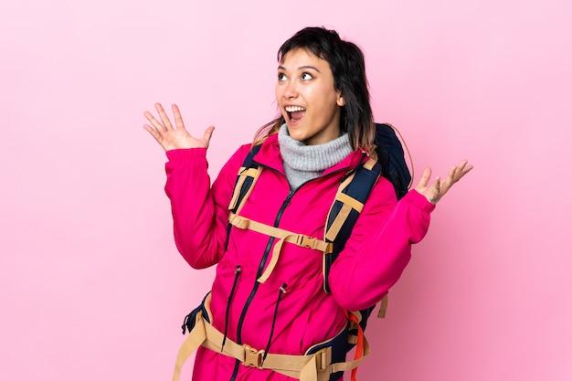 Góral młoda dziewczyna z dużym plecakiem na pojedyncze różowe z niespodzianką wyraz twarzy