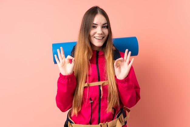 Góral młoda dziewczyna z dużym plecakiem na różowej ścianie pokazano ok znak palcami