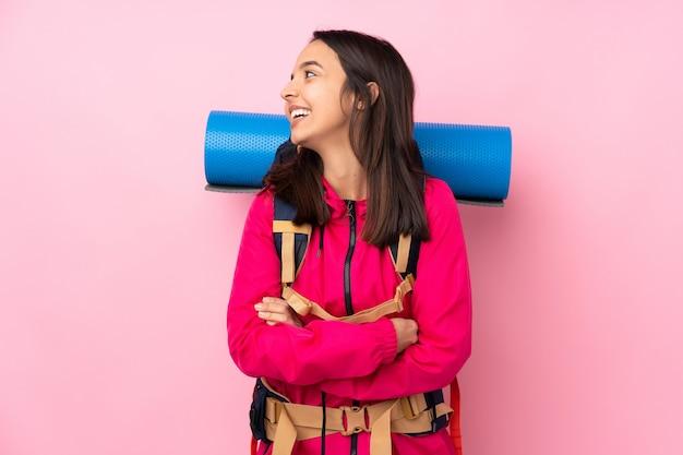 Góral młoda dziewczyna z dużym plecakiem na różowym szczęśliwy i uśmiechnięty