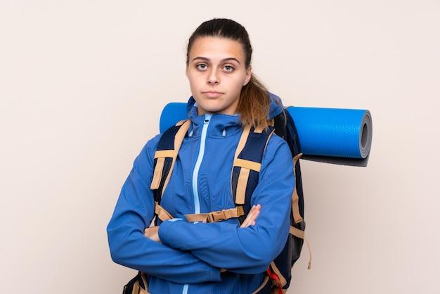 Góral młoda dziewczyna z dużym plecakiem, trzymając ręce skrzyżowane