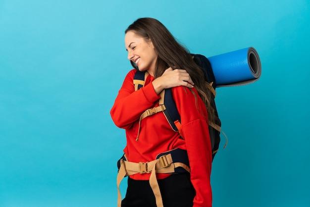 Góralska kobieta z dużym plecakiem na odizolowanej ścianie cierpiąca na ból ramienia z powodu wysiłku