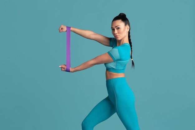 Górna część ciała. piękna młoda lekkoatletka ćwicząca w studio, monochromatyczny niebieski portret