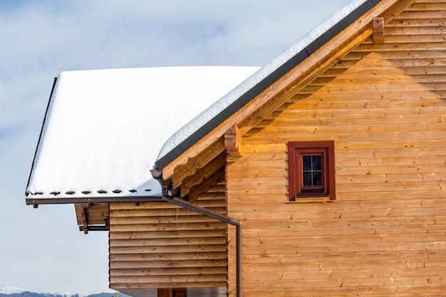 Górna część drewnianego ekologicznego tradycyjnego domku z materiałów drewnianych ze stromym dachem, pokoje na poddaszu pokryte śniegiem w słoneczny zimowy dzień. stare tradycje i nowoczesna profesjonalna koncepcja budowy.