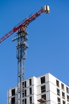 Górna część niebieskiego i czerwonego żurawia wieżowego w pobliżu nowego budynku na błękitnym niebie, selektywna ostrość