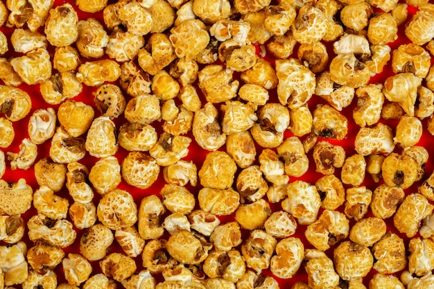 Górna karmelizowana kukurydza pop na czerwonym