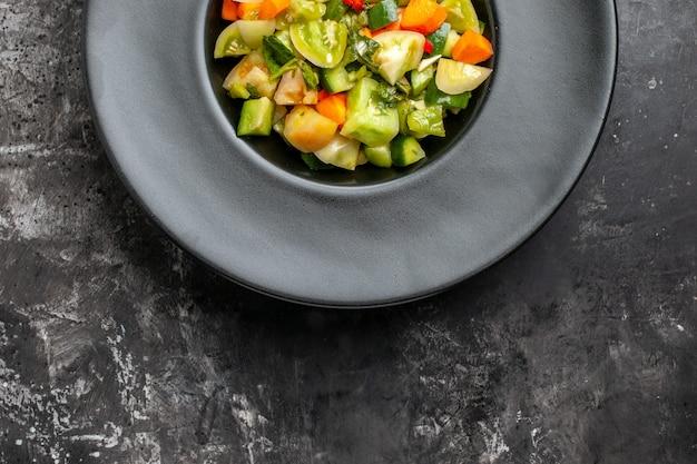 Górna połowa widoku zielona sałatka z pomidorów na owalnym talerzu na ciemnym tle
