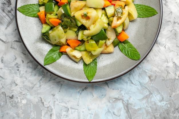 Górna połowa widoku zielona sałatka z pomidorów na owalnym talerzu na szarym tle