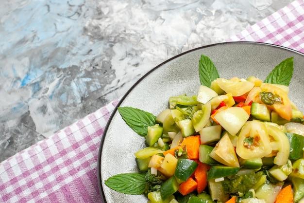 Górna połowa widoku zielona sałatka z pomidorów na owalnym talerzu różowy obrus na szarym tle