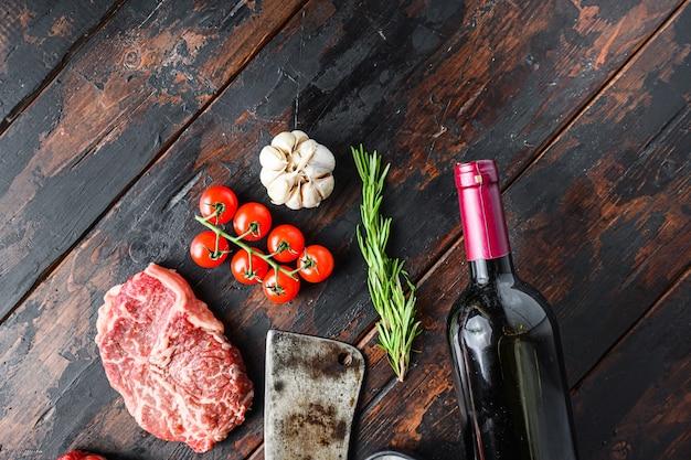 Górne ostrze organicznego mięsa, surowy marmurkowy stek wołowy, ze starym tasakiem rzeźniczym, butelką czerwonego wina i przyprawami na ciemnym drewnianym stole w stylu rustykalnym, widok z góry z miejscem na tekst.