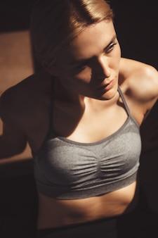 Górne zdjęcie wysportowanej blondynki odpoczywającej na podłodze w stroju sportowym