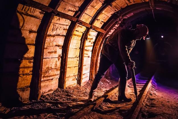 Górnik pracuje młot pneumatyczny w kopalni węgla. pracuj w kopalni węgla. portret górnika. skopiuj miejsce