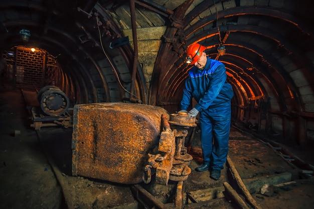 Górnik w kopalni węgla stoi w pobliżu wózka. skopiuj miejsce. górnik naprawia wózek