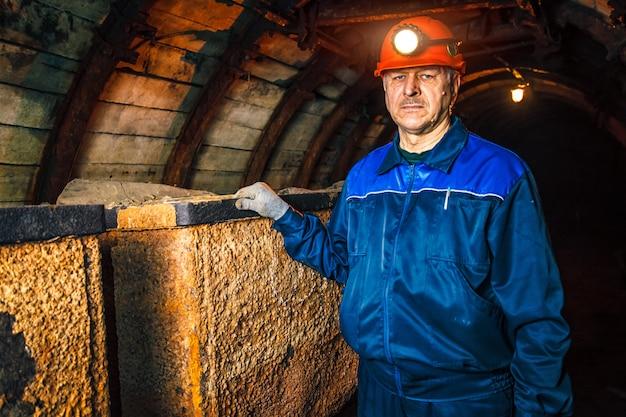 Górnik w kopalni węgla stoi w pobliżu wózka. skopiuj miejsce.