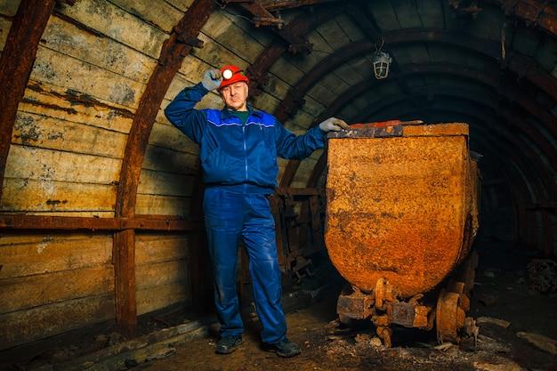 Górnik w kopalni węgla stoi w pobliżu wózka.