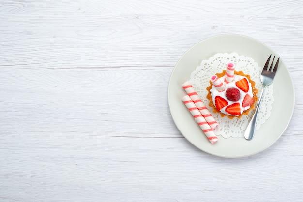 Górny daleki widok małego ciasta ze śmietaną i pokrojonymi truskawkami wewnątrz płyty na białym, słodkim cukrze jagodowym