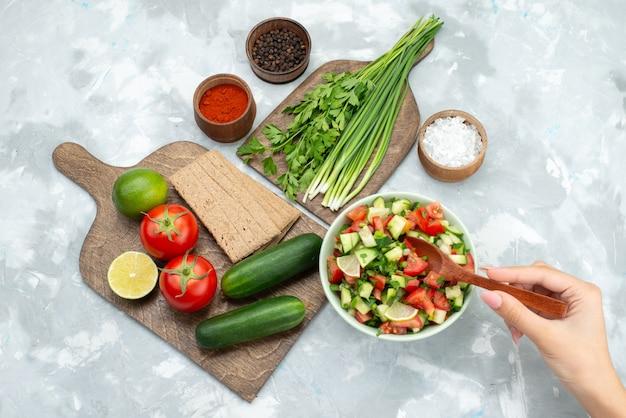Górny stół do dalekiego widoku z warzywami, takimi jak pomidory, ogórki, a wraz z chipsami cytrynowymi i zieleniną na białym, sałatkowym jedzeniu warzywnym