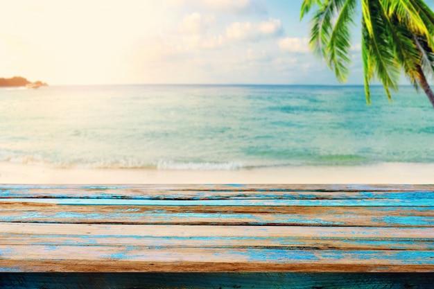 Górny stół drewna na rozmyte morze z drzewa kokosowego tła - pusty gotowy do montażu produktu wyświetlacz. koncepcja plaży w lecie. vintage kolorystyka