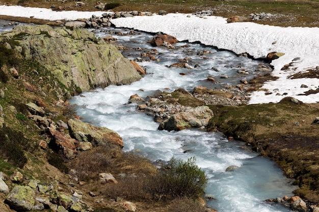 Górska rzeka w przełęczy susten położona w szwajcarii zimą w ciągu dnia