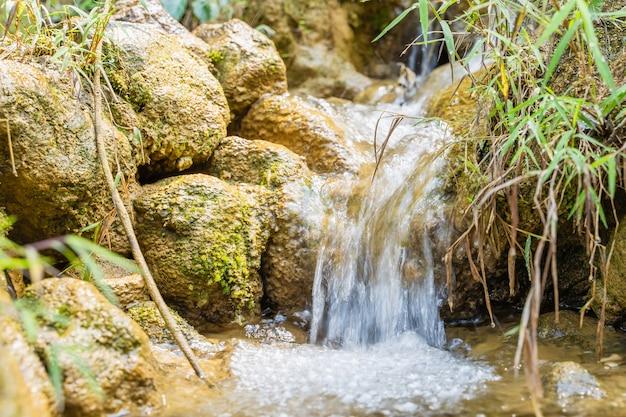 Górska rzeka z kamiennymi kaskadowymi wodospadami. naturalne tło w słoneczny dzień. obraz referencyjny do malowania cyfrowego.