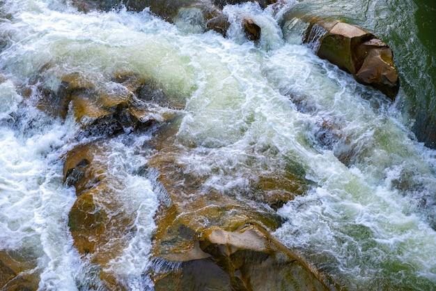 Górska rzeka z małym wodospadem z czystą turkusową wodą opadającą między mokrymi głazami z gęstą białą pianą.