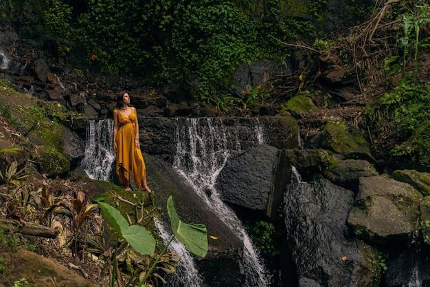 Górska rzeka. zachwycona kobieta słuchająca odgłosów wody podczas spaceru po lesie