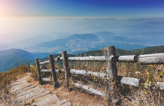 Górska sucha łąka, chmury mgły oraz drewniany płot i chodnik.