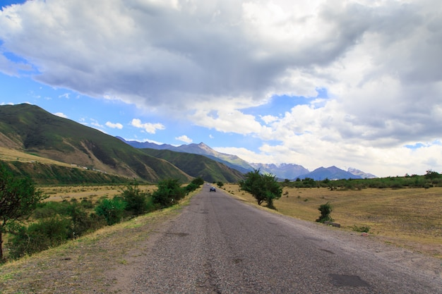 Górska wiejska droga wśród zielonych wzgórz