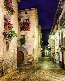 Górska wioska nocą. architektura kamiennych domów, balkonów z kwiatami i oświetlonych alejek. torla ordesa.