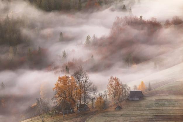 Górska wioska w chmurach mgły i dymu jesienią