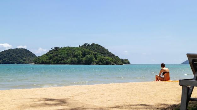 Górska wyspa nad morzem z turystą usiąść na plaży po prawej stronie z jasnym niebem