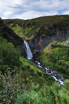 Górski krajobraz półwyspu kamczatka: widok na malowniczą dolinę, głęboki kanion i kaskadę górskiego wodospadu otoczone skalistymi zboczami, bujną roślinność wysokogórską - zielone krzewy i drzewa.