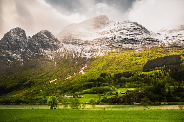 Górski krajobraz w słoneczny dzień. podróżuj po europie. wiosna w norwegii. piękne zielone pole w skandynawii. piękny krajobraz z widokiem na góry. turystyka w europie. charakter tła