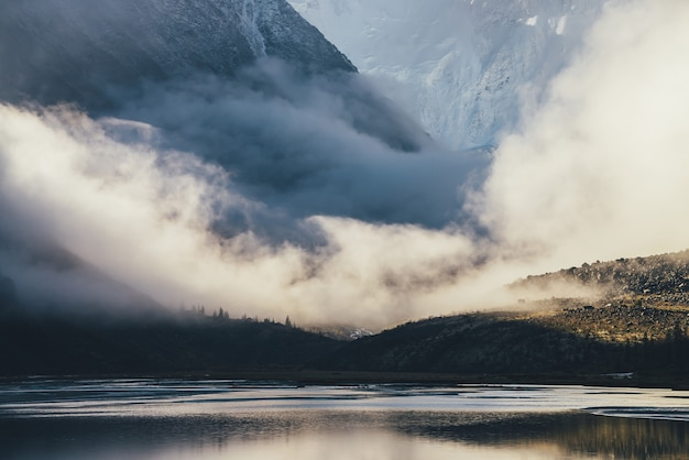 Górski krajobraz z błyszczącym jeziorem i sylwetkami drzew iglastych na ciemnych skałach z widokiem na wysoką ośnieżoną ścianę górską w niskich chmurach w złotym słońcu. warstwowa sceneria z cieniem i światłem słonecznym.