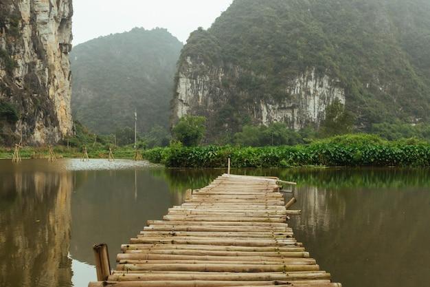 Górski krajobraz z drewnianym mostem i jeziorem, ninhbinh, wietnamska panorama w trang an