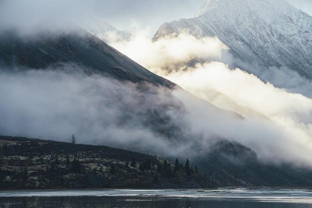 Górski krajobraz z jeziorem i sylwetkami drzew iglastych na omszałym wzgórzu z widokiem na wysoką śnieżną górę w niskich chmurach w złotym słońcu. warstwowa sceneria z cieniem i światłem słonecznym w górach.