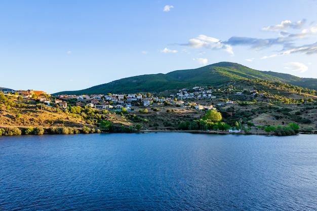 Górski krajobraz z turkusowym jeziorem i wioską.