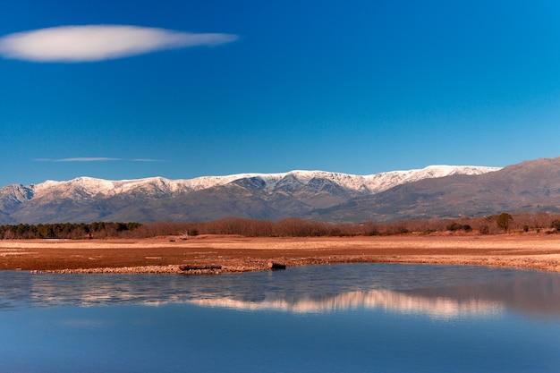 Górski krajobraz ze śniegiem na szczytach odbijającym się w wodzie jeziora