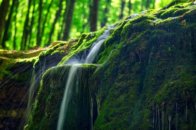 Górski potok w słońcu na długiej ekspozycji z pięknymi śladami od spadających kropli.