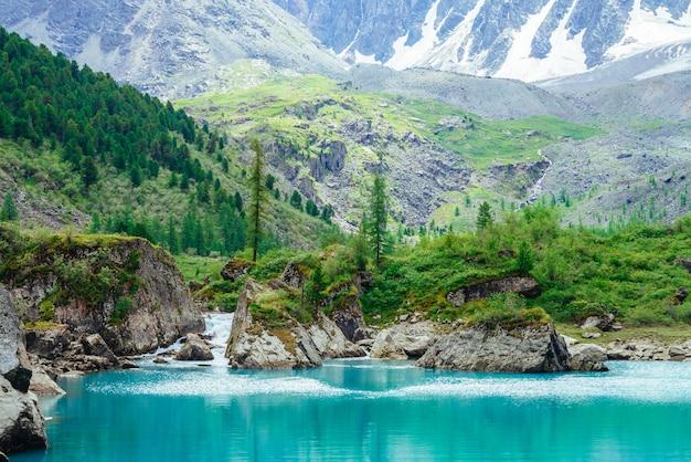 Górski potok z lodowca wpada do lazurowego jeziora. szybki przepływ czystej wody z potoku. cudowne skały z bogatą roślinnością wyżynną. piękne drzewa iglaste. niesamowity krajobraz majestatycznej przyrody.
