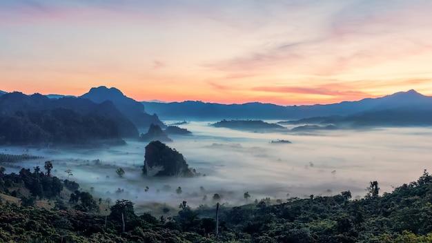 Górski wschód słońca z pięknym dramatyczne niebo. rano mgła w górskiej dolinie przed wschodem słońca w sezonie zimowym.phu langka górski krajobraz z porannym morzem mgły w tle