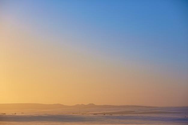 Górski zimowy krajobraz niebieskiego nieba o zachodzie słońca