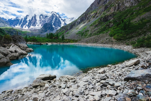 Górskie jezioro otoczone jest dużymi kamieniami i głazami przed gigantycznym pięknym lodowcem. niesamowite zaśnieżone góry. grzbiet ze śniegiem. cudowny klimatyczny krajobraz majestatycznej przyrody wyżyn.