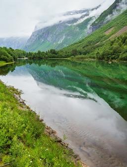 Górskie jezioro z czystą przezroczystą wodą i odbiciem skały w nieruchomej powierzchni wody